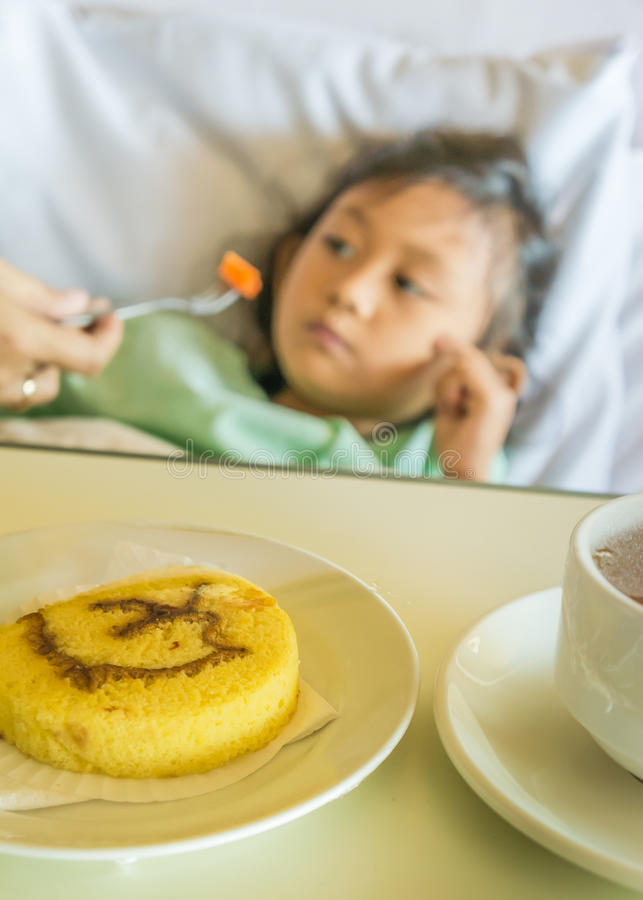 Patient hospitalisé asiatique malade d'enfant mangeant sur le lit photographie stock libre de droits