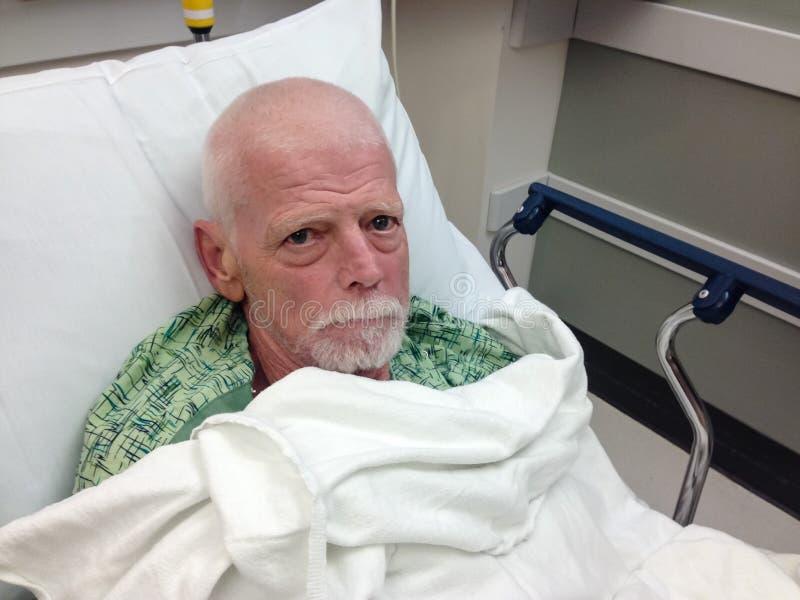 Patient hospitalisé supérieur masculin dans le lit d'hôpital photo libre de droits