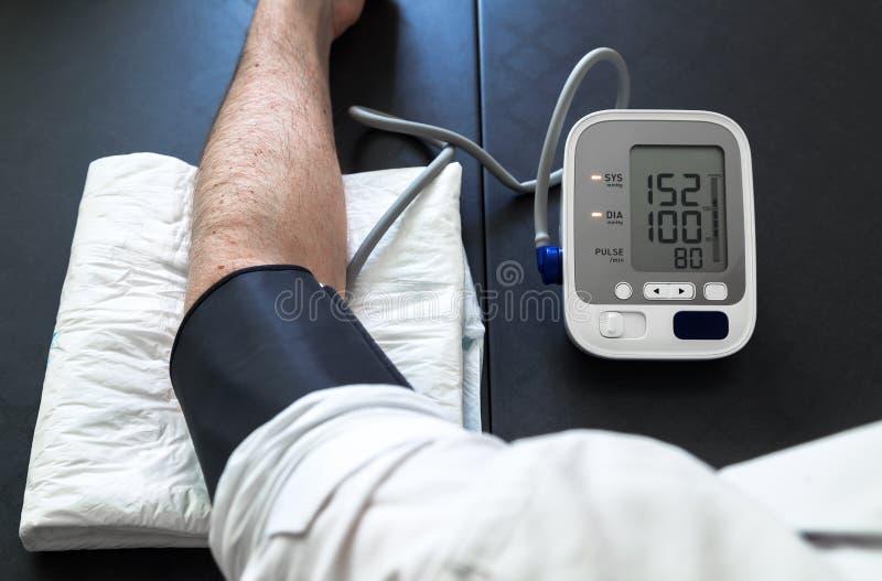Patient hypertendu réalisant un essai automatique de tension artérielle photos libres de droits