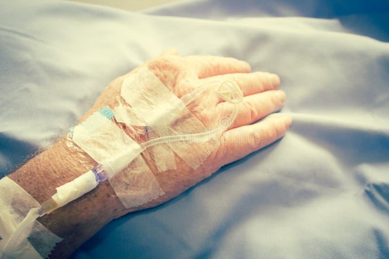 Patient i sjukhussäng och att ha Iv-lösningsdroppe arkivbild
