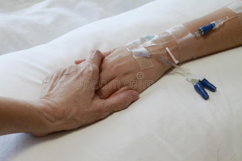 Patient with IV Drip. An older hand holding that of a patient with an intravenous drip royalty free stock photography