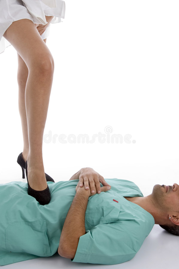 Patient keeping leg on doctor's chest stock image