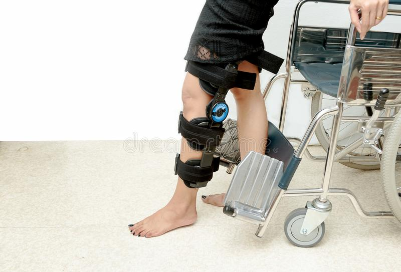 Patient on knee brace support try to walk training,Rehabilitation treatment royalty free stock photo