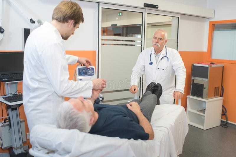 Patient laying on bed and doctors checking on him. Patient stock image