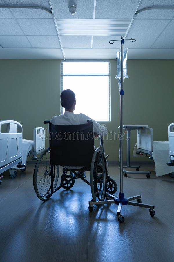 Patient looking through window while sitting in wheelchair in hospital stock photo