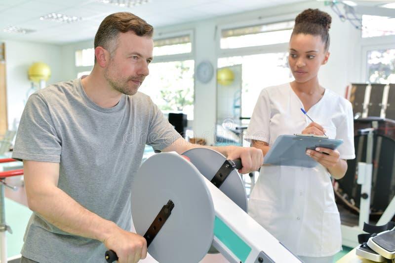 Patient masculin avec le physio- thérapeute féminin établissant des bras image stock