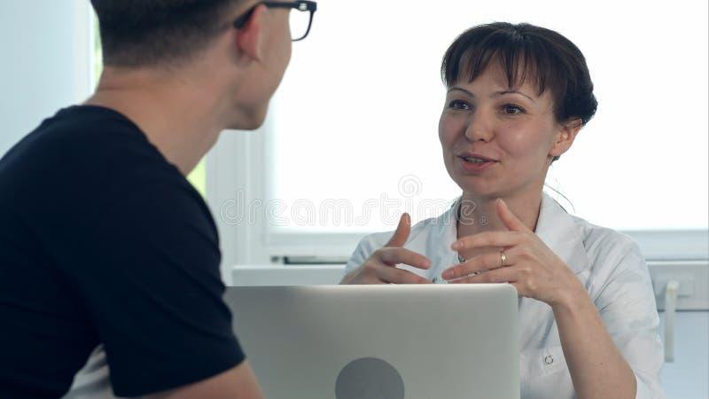 Patient masculin de consultation de docteur féminin amical s'asseyant au bureau avec l'ordinateur portable photos libres de droits