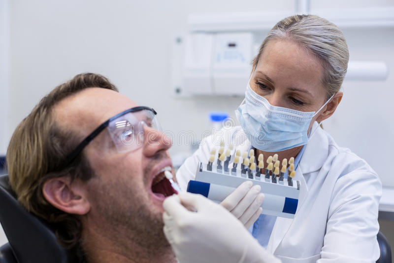 Patient masculin de examen de dentiste féminin avec des nuances de dents image libre de droits
