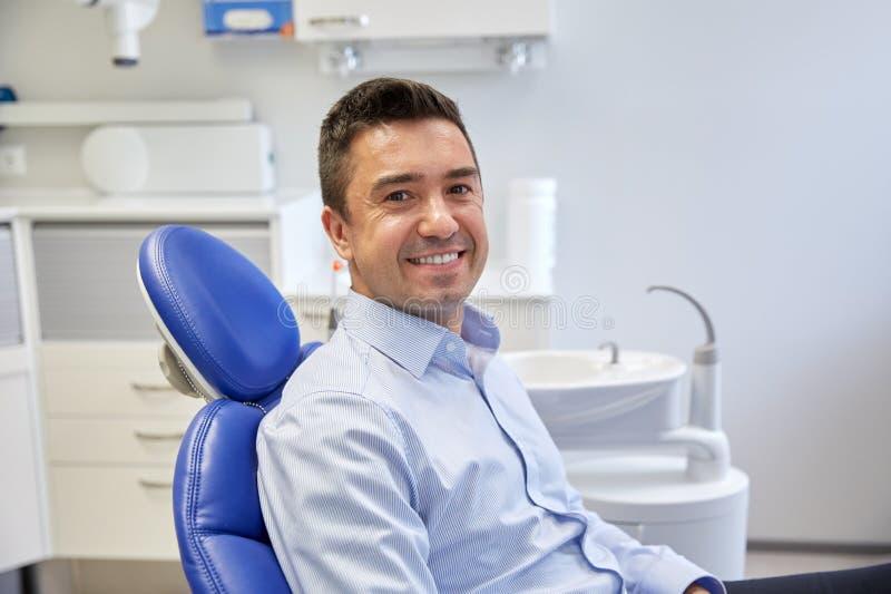 Patient masculin heureux s'asseyant sur la chaise dentaire photo libre de droits