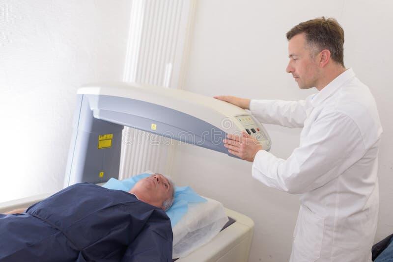 Patient masculin mûr de technicien radiologique se trouvant sur le lit de balayage photographie stock libre de droits