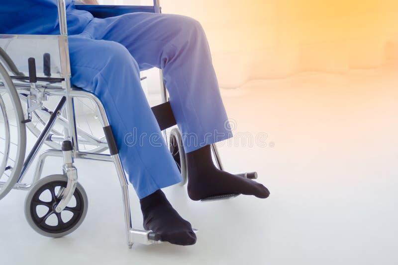 Patient masculin s'asseyant sur le fauteuil roulant dans l'hôpital image stock