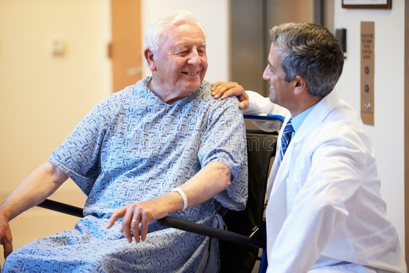Patient masculin supérieur étant enfoncé le fauteuil roulant par le docteur photographie stock