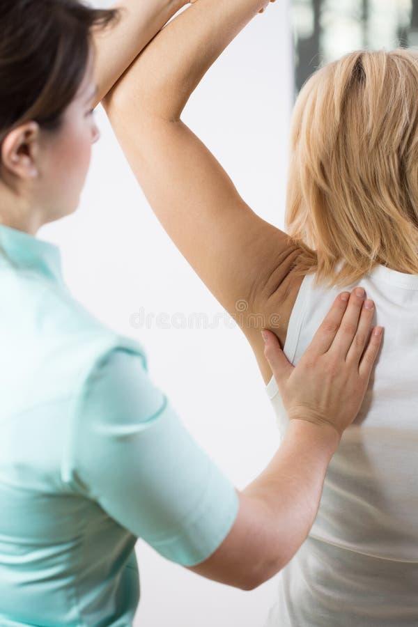 Patient med den smärtsamma armen fotografering för bildbyråer