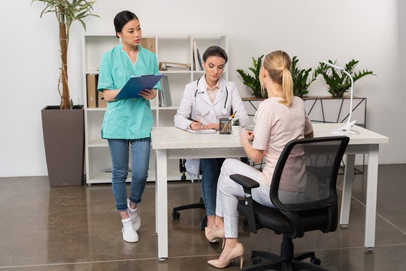 Patient mit Doktor und Internisten, die bei Tisch während der Beratung in der Klinik sitzen lizenzfreies stockbild