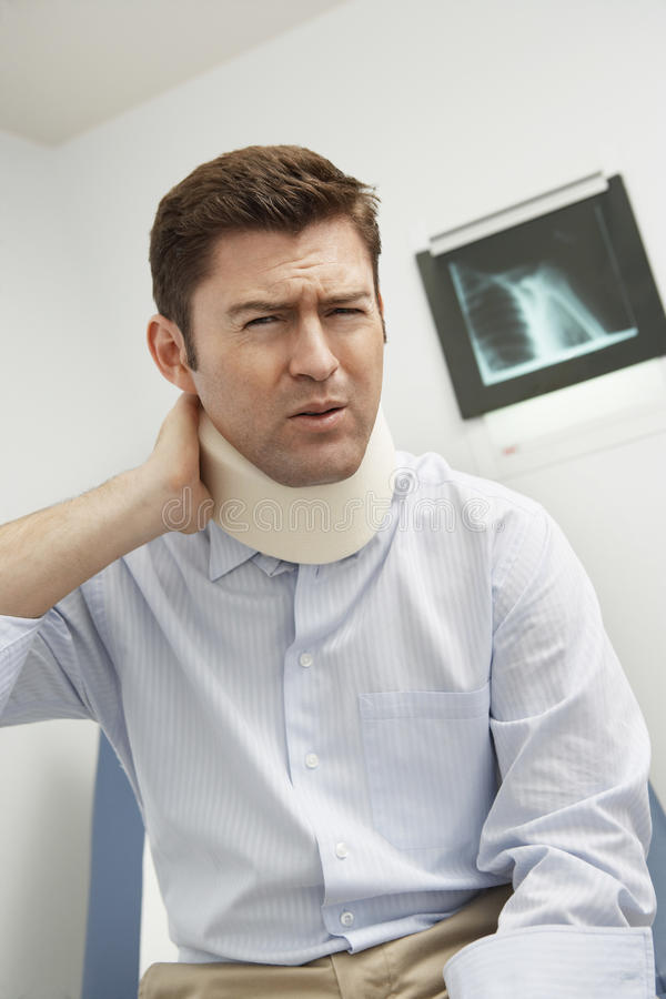Patient In Neck Brace. Portrait of a young male patient in neck brace stock photos