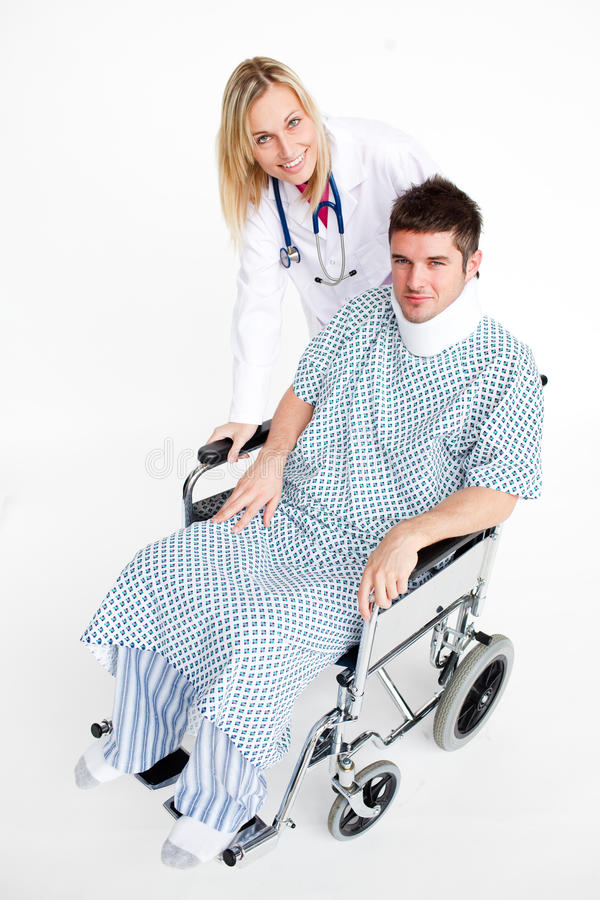 Patient with a neck brace and beautiful doctor. Patient sitting in a wheelcchair with a neck brace and beautiful doctor royalty free stock image