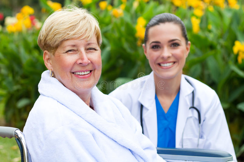 Patient and nurse. Caring friendly nurse and happy senior patient portrait outdoors royalty free stock photos
