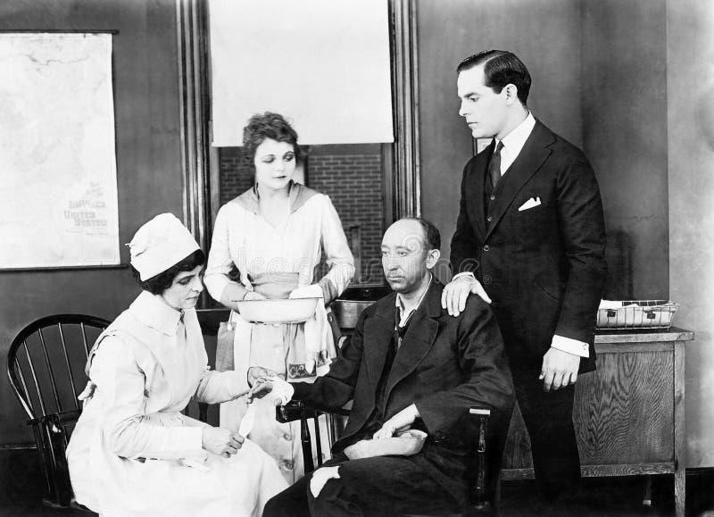 Patient och två sjuksköterskor som deltar i honom och en vän som tröstar honom (alla visade personer inte är längre uppehälle, oc arkivbild