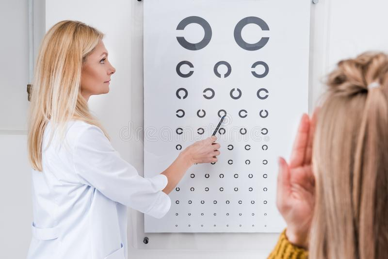 Patient and optician doing Eye test with eye chart. In clinic royalty free stock photos