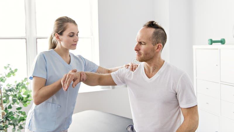Patient på sjukgymnastiken som gör fysiska övningar med hans terapeut arkivbilder