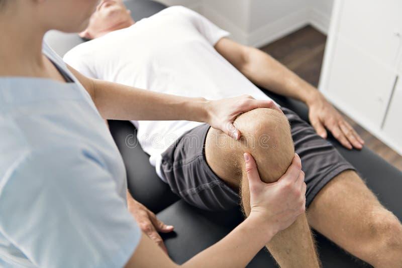 Patient på sjukgymnastiken som gör fysiska övningar med hans terapeut royaltyfri bild