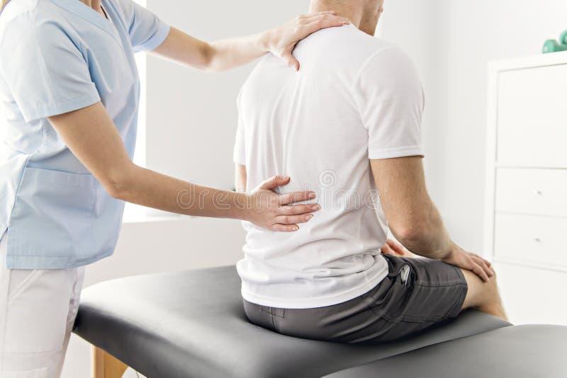 Patient på sjukgymnastiken som gör fysiska övningar med hans terapeut arkivfoton