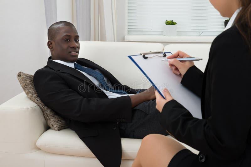 Patient på soffan och psykiatern Writing On Clipboard royaltyfri bild