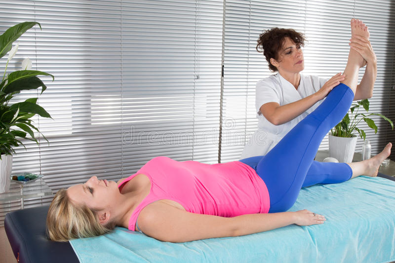 Patient at the physiotherapy doing physical exercises with her therapist stock image