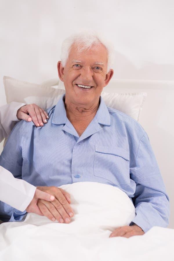 Patient plus âgé de sourire dans le lit photographie stock