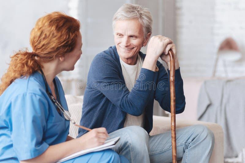 Patient plus âgé gai parlant au travailleur médical photos stock