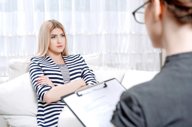 Patient at psychological therapy session. Young blond women sitting on a couch with her arms crossed telling about her problems, doctor with clipboard listening royalty free stock photo