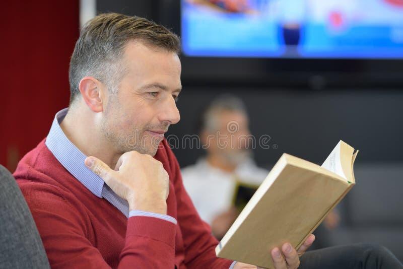 Patient reading book in doctors waiting room stock image