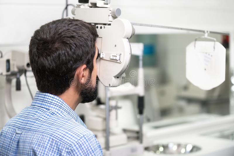 Patient is reading the optometrist chart in modern ophthalmology clinic. stock photo
