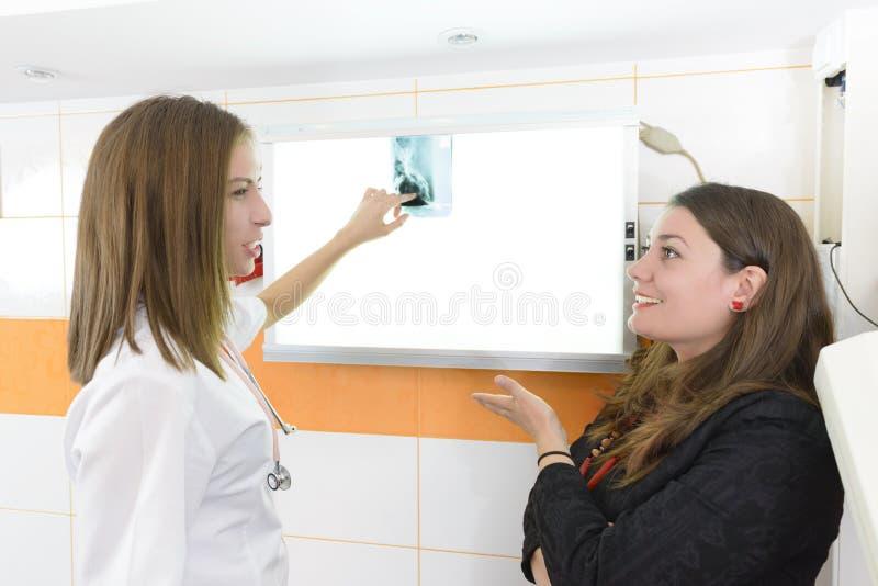 Patient regardant avec le docteur l'image de rayon X photo libre de droits