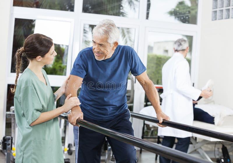 Patient regardant le physiothérapeute féminin While Walking Between photo libre de droits
