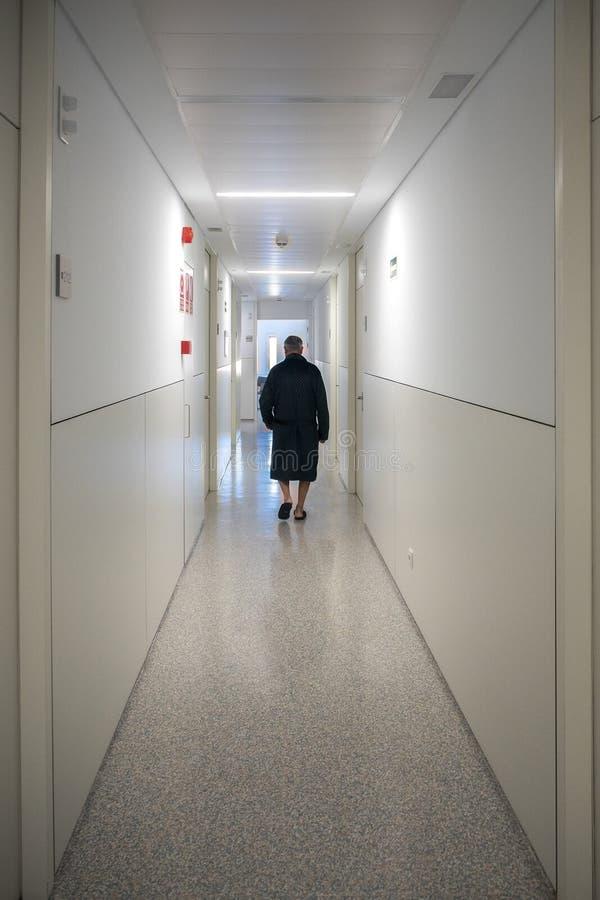 Patient seul marchant dans un couloir d'hôpital photo stock