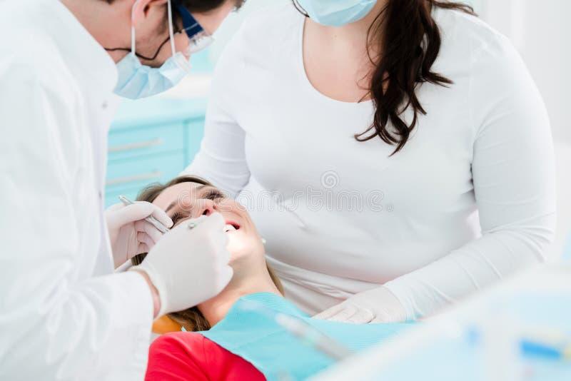 Patient som behandlas av tandläkaren i hans kirurgi arkivbilder