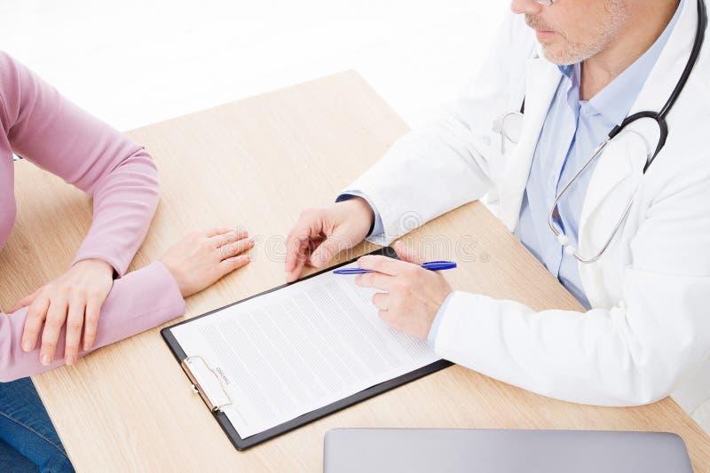 Patient som fast beslutsamt lyssnar till en manlig doktor som förklarar tålmodiga tecken eller frågar en fråga, som de diskuterar royaltyfri bild