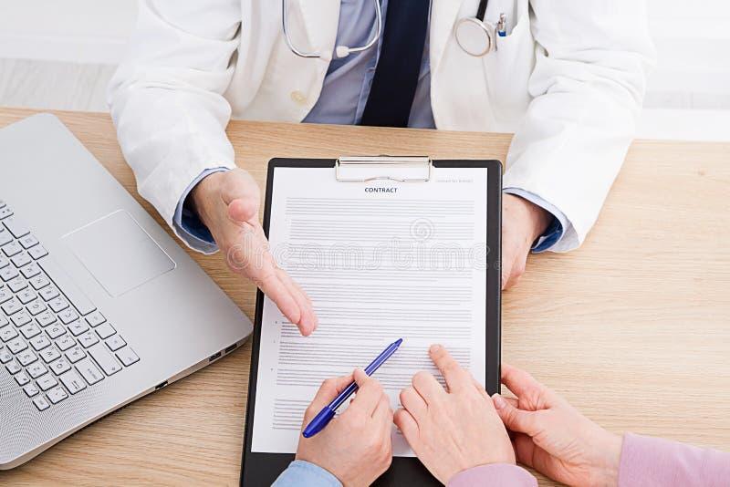 Patient som fast beslutsamt lyssnar till en manlig doktor som förklarar tålmodiga tecken eller frågar en fråga, som de diskuterar arkivfoto