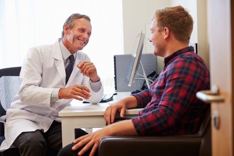 Patient som har konsultation med manlig doktor In Office royaltyfri bild