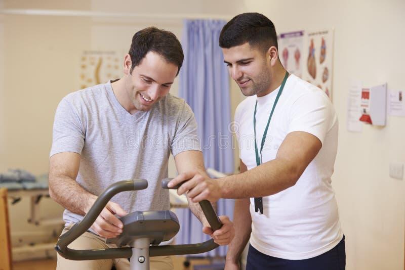 Patient som har sjukgymnastik på motionscykelen i sjukhus arkivfoton