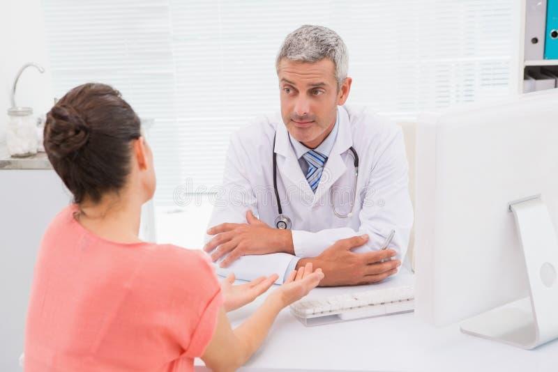 Patient som konsulterar en allvarlig doktor arkivfoton