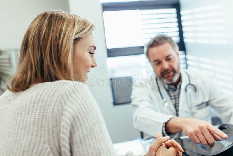 Patient som talar med doktorn under en konsultation fotografering för bildbyråer