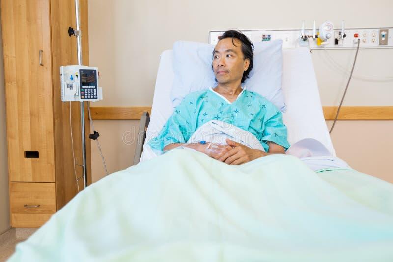 Patient som vilar på säng, medan se bort in royaltyfri foto