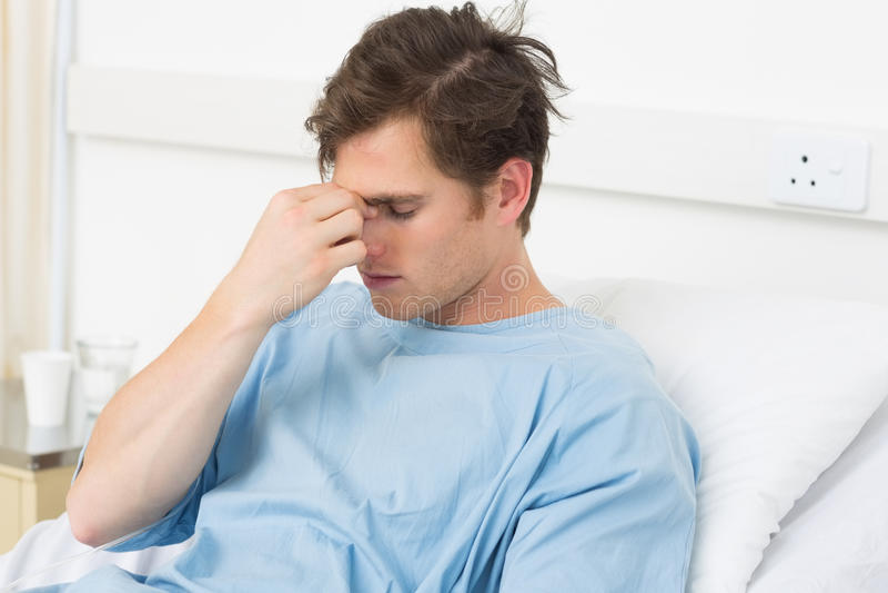 Patient souffrant du mal de tête détendant dans l'hôpital photographie stock