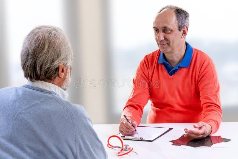 Patient supérieur à la consultation du docteur s Clinique, hôpital, soins de santé et médecine photographie stock