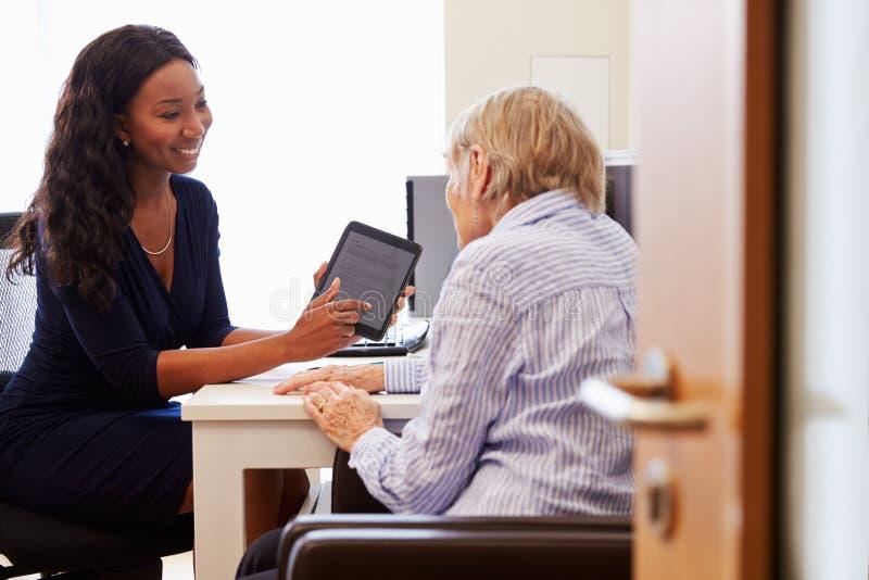 Patient supérieur ayant la consultation avec docteur In Office photos stock