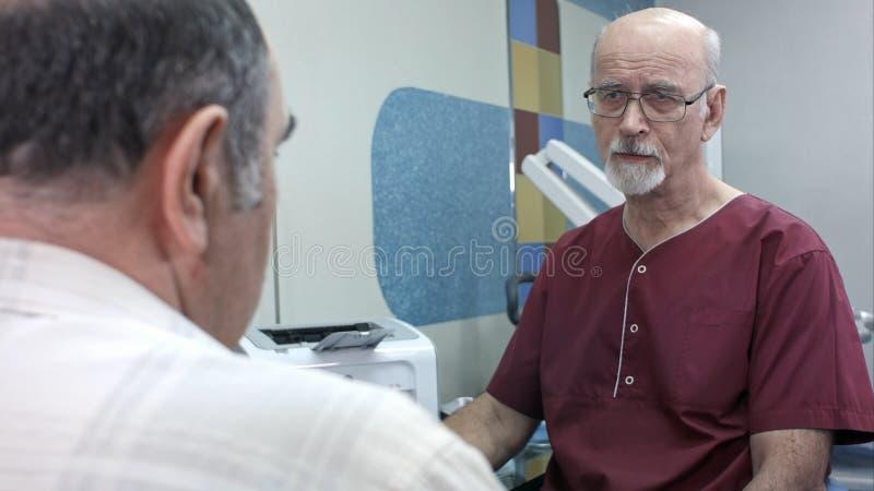 Patient supérieur ayant la consultation avec le docteur dans l'hôpital image stock