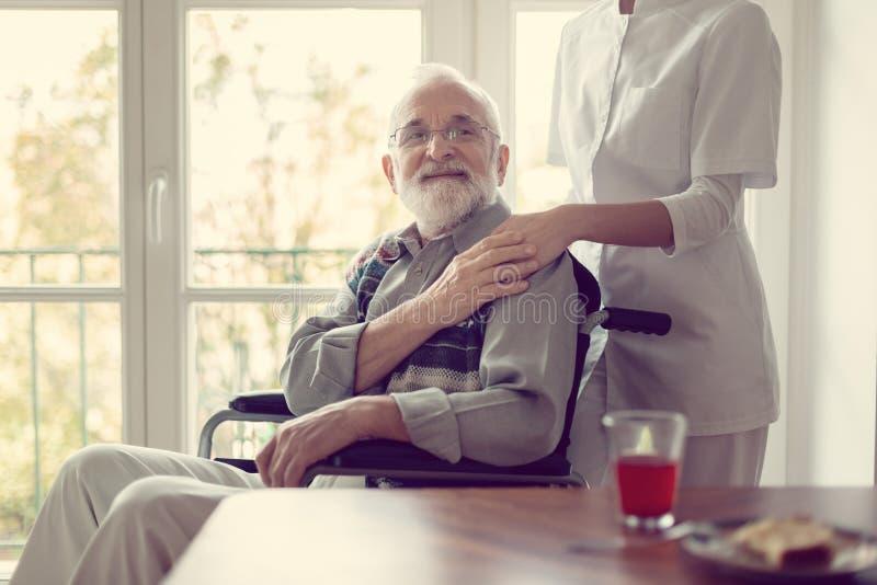 Patient supérieur dans la maison de repos avec l'infirmière utile dans l'uniforme blanc photo stock