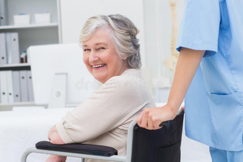 Patient supérieur dans le fauteuil roulant poussé par l'infirmière image libre de droits